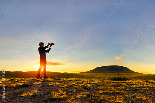 Foto Man Photographing On Land Against Sky At Sunset