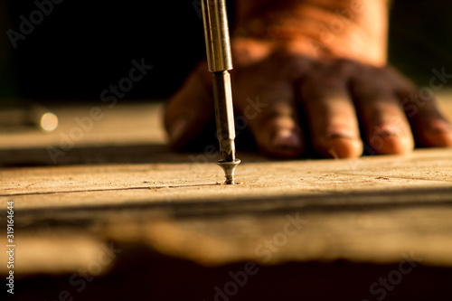 Obraz Close-Up Of Man Screwing Nail In Wood - fototapety do salonu