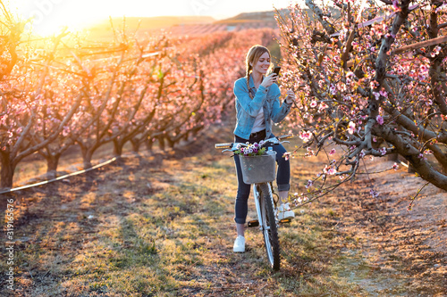 Pretty young woman with a vintage bike taking photographs of cherry blossoms on the field in springtime.