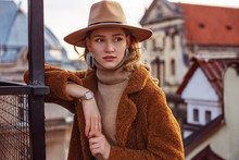 Outdoor Fashion Portrait Of Elegant Woman Wearing Beige Hat, Wrist Watch, Turtleneck, Brown Faux Fur Coat, Trendy Big Earrings With Rhinestones, Posing In European City. Copy, Empty Space For Text