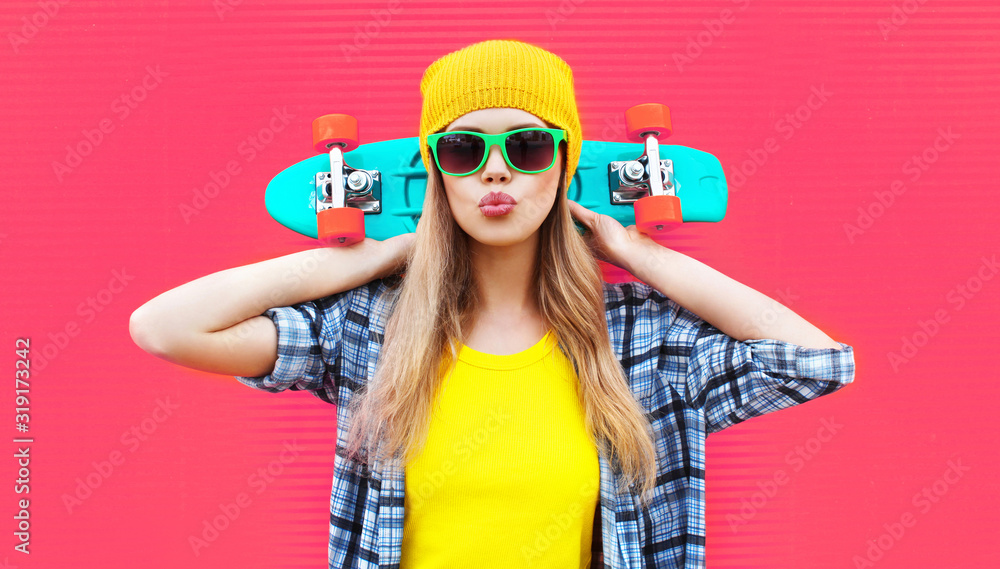 Fototapeta Portrait cool woman with skateboard wearing colorful yellow hat on pink background