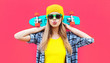 canvas print picture - Portrait cool woman with skateboard wearing colorful yellow hat on pink background