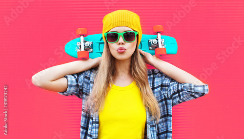 Cuadros en Lienzo Portrait cool woman with skateboard wearing colorful yellow hat on pink backgrou