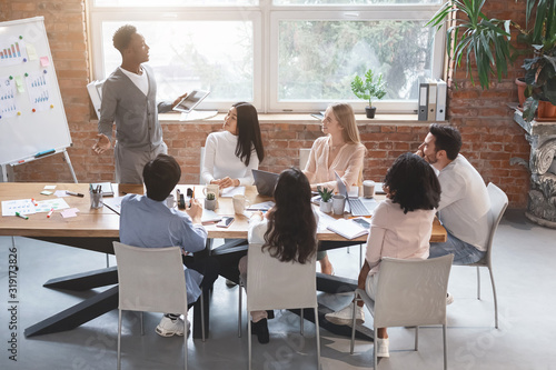 Black guy with digital tablet sharing business ideas with colleagues