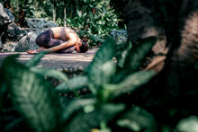 Free Your True Self. Full-length Shot Of Caucasian Woman Sitting In Child's Pose, Balasana While Practicing Yoga Outdoors, In A Garden. Healthy Lifestyle And Relaxation Concept