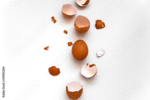 top view flat lay one brown egg and egg shells on a white background Wallpaper Mural