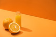 canvas print picture - fresh juice in glass bottle near oranges on orange background