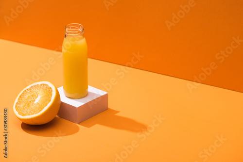 Fototapeta fresh juice in glass bottle near orange half and white cube on orange background obraz