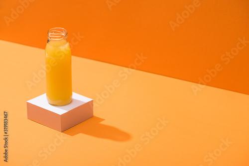fresh juice in glass bottle on white cube on orange background