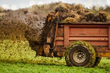 Farmer Spreading Manure In Fields In Autumn