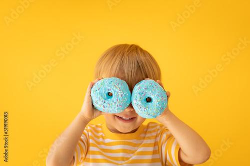 Fototapeta Happy child holding glazed donut obraz