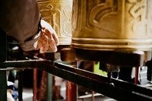 Cropped Hand Of Man Touching Prayer Wheels In Temple