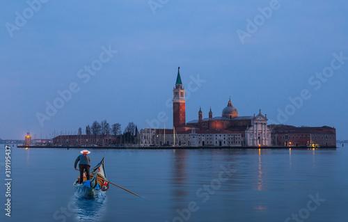 Fotografie, Obraz Venetian gondolier punting gondola through grand canal waters - View of San Gior