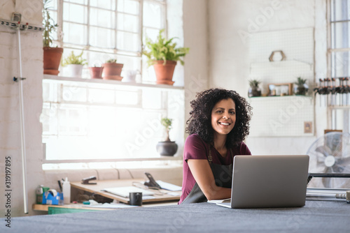 Smiling young woman using a laptop in her framing shop Fototapete