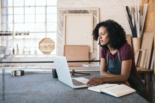 Female entrepreneur using a laptop in her framing shop Fototapete