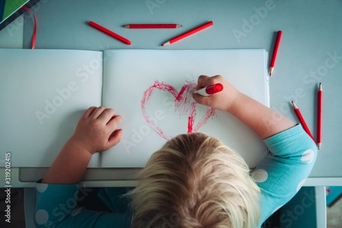 Foto Little girl drawing red heart at white paper within red pens and pencils