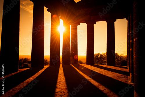 Fotografie, Tablou SUNLIGHT STREAMING THROUGH SILHOUETTE OF BUILDING