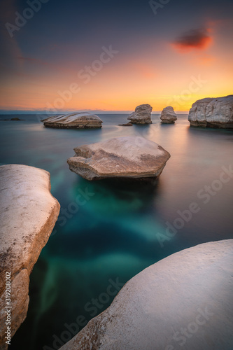 Obraz Beautiful sunset at the rocky beach near Limassol Cyprus with smooth water and white rocks standing out of water - fototapety do salonu
