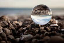 Close-Up Of Crystal Ball On Stones At Beach