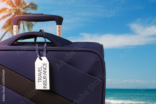 Photo Blue suitcase with Travel Insurance label closeup