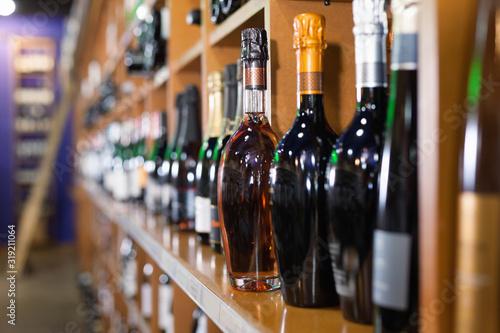 Fotografia Rows of wine bottles on shelves in modern wine store waiting for customers