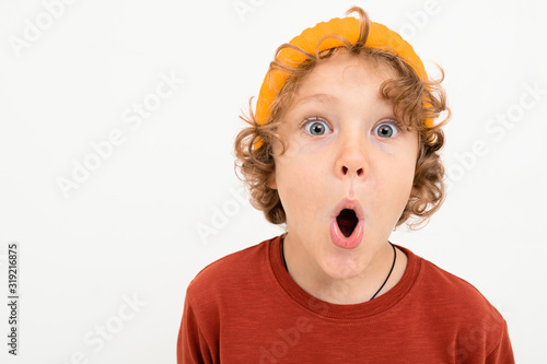 Obraz Portrait of charming boy with curly hair, yellow hat is scared isolated on white background - fototapety do salonu