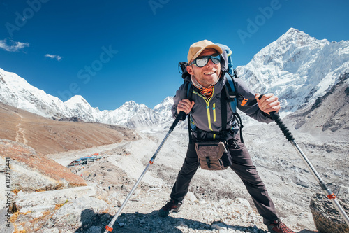 Portrait of smiling Hiker man with Nuptse 7861 m peak and Gorak shep settlement background with trekking poles, UV protecting sunglasses Canvas Print