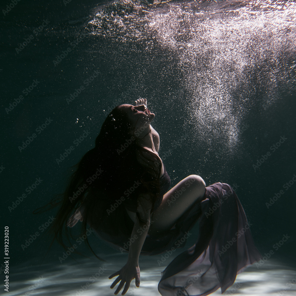 Beautiful girl swims underwater in the pool with a scarf or in a dress. Brunette with dark and long hair. Dark tones of water and atmosphere