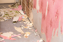 Removing Old Retro Style Wallpaper From Concrete Wall. Home Renovation Concept.