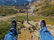 Between Two Legs A View Of A Pillar And Chair Lifts And A Mountain Valley