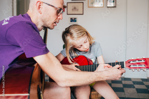Obraz na plátně father teaching to his daughter how to play guitar