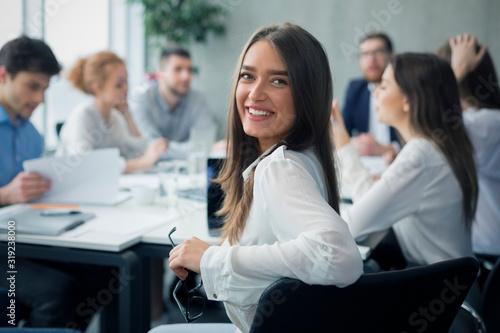 Obraz Positive secretary smiling to camera during meeting - fototapety do salonu