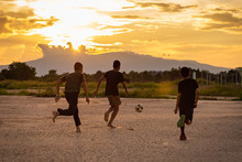 Silhouette Action Sport Outdoors Of Kids Having Fun Playing Soccer Football For Exercise In Community Rural Area Under The Twilight Sunset. Poor And Poverty Children In Development Country.