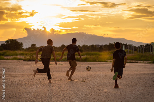 Silhouette action sport outdoors of kids having fun playing soccer football for exercise in community rural area under the twilight sunset Canvas Print