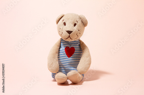 plush toy soft bear on a pastel pink background, close-up.