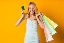 Shopping Concept. Overjoyed Woman Holding Credit Card And Paper Bags