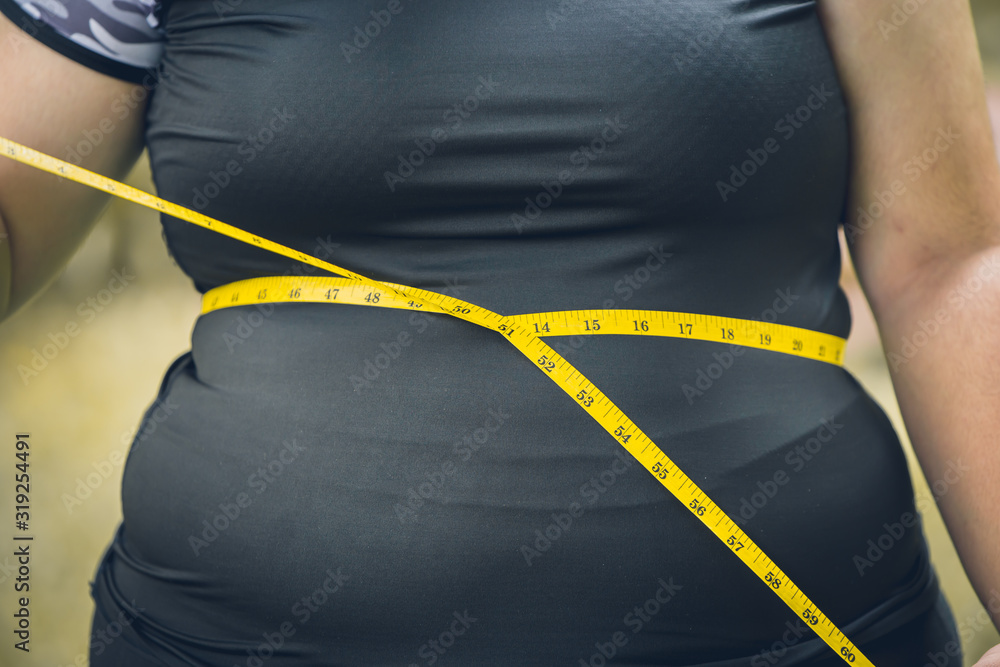 Fototapeta girl waist belly fat woman with waist tape measure closeup shot.
