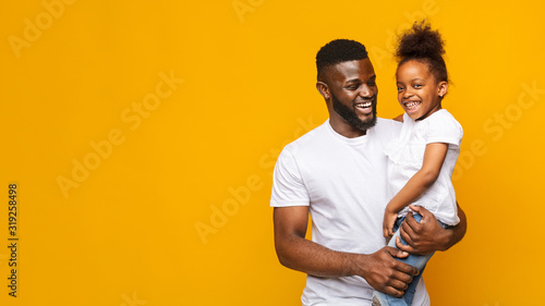 Happy african man holding little daughter over yellow background Wallpaper Mural