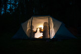 Children making shadow puppets in a camping tent at night
