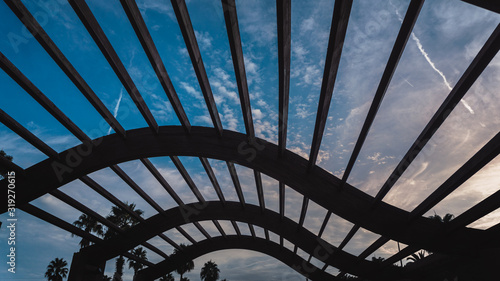 Fotografia Detail of a pergola wave shaped with a cloudy sky of in the background