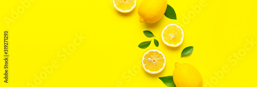Photographie Creative background with fresh lemons and green leaves on bright yellow background