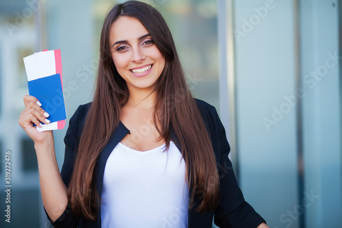 Fotomural Woman holding two air ticket in abroad passport near airport