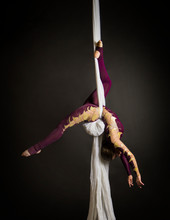 Sporty Girl In A Burgundy Suit Performs Gymnastic And Circus Exercises On White Silk.