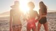 Rear view of three beautiful women walking on beach