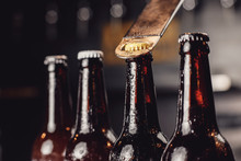 Glass Ice Cold Bottles Of Beer With Opener Cap On Dark Background