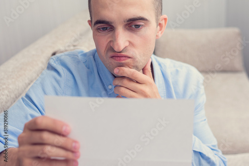Photo Dissatisfied guy reading a letter, guy sitting on the couch, copy space, portrai