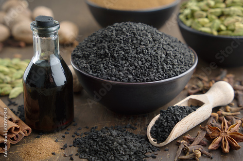 Fototapeta Black cumin or roman coriander seeds and black caraway oil bottles, aromatic spices on table: cardamom, anise, cloves, cinnamon,  turmeric. Ingredients for cooking. Ayurveda treatments. obraz