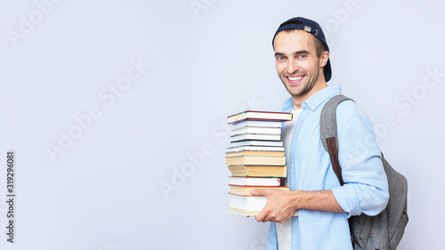 Photo Happy student guy with backpack carries a stack of books on gray background, cop