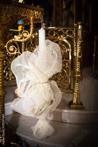 Vászonkép Beautiful white decorated orthodox baptismal candle hanging on a church