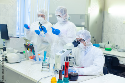 Scientists in protective suits in a science laboratory study a dangerous virus to eliminate the epidemic Wallpaper Mural